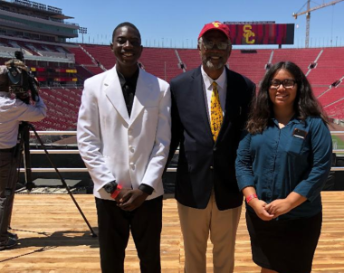 Two professionally dressed young adults stand next to a man in a suit jacket in a sports stadium