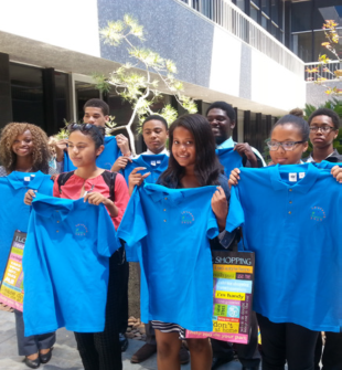 A group of young students standing outside holding blue t-shirts
