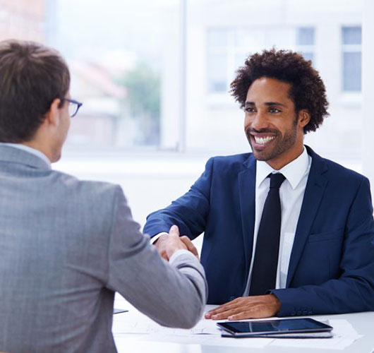 A man shaking hands with a potential employer during an interview